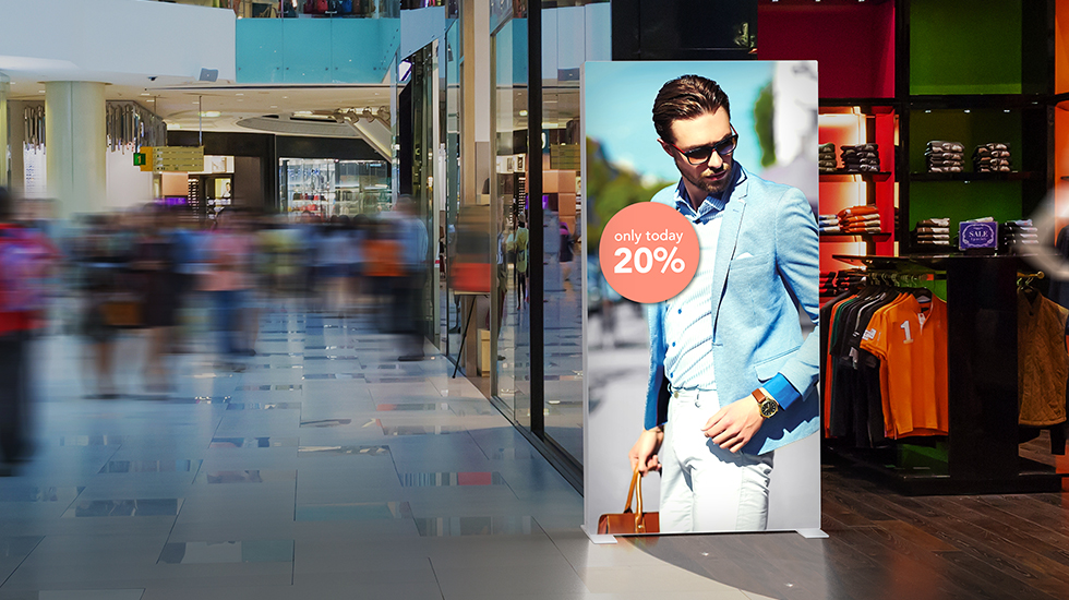 Mobile PIXLIP GO illuminated frame with illuminated advertising motif in a lively shopping mall