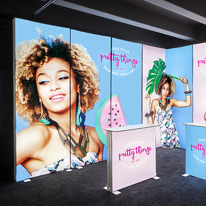 Exhibition hall with a luminous fair booth made of colourful printed lightwalls by Pixlip Go