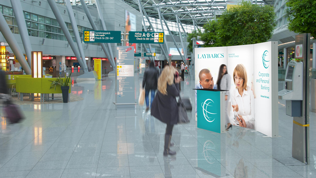 Promotion stand made of luminous Pixlip Go frames with multicolored textiles in a busy airport terminal