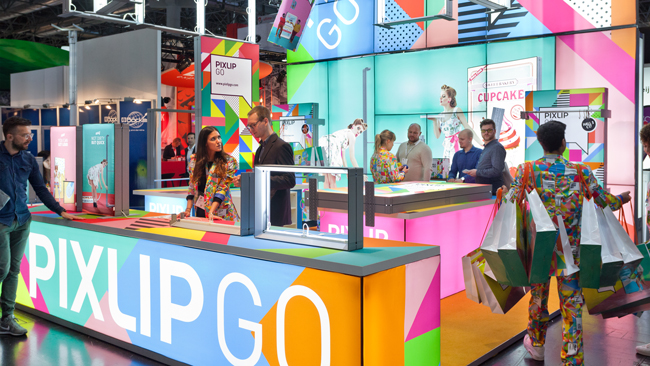 Colourfull illuminated PIXLIP GO fair booth at the Euroshop 2017 with a lot of visitors
